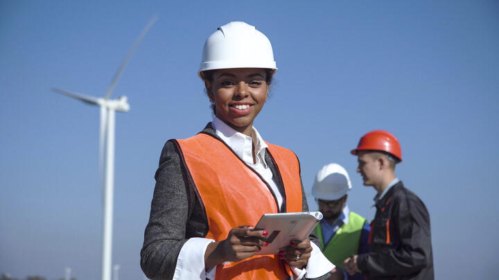 engineer looking at the camera smiling in an open windmill field