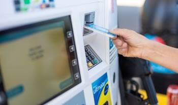 woman inserting credit card on the gasoline dispenser